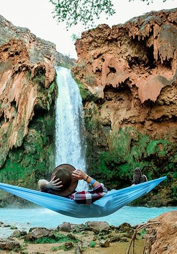 Mann in einer Hängematte vor einem Wasserfall