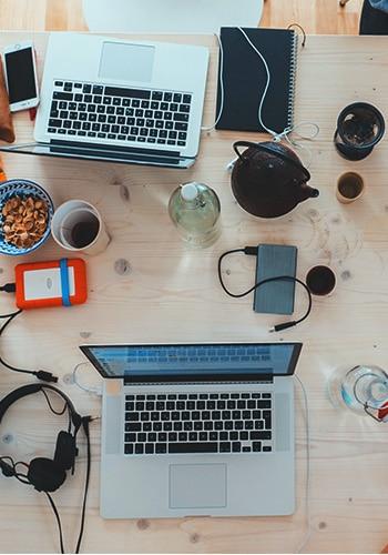 Arbeitsplatz mit vielen Laptops und Kaffee Arbeit Nachhaltig